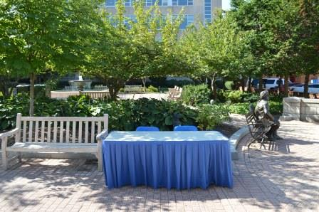 Outdoor table with blue table skirt surrounded by green trees