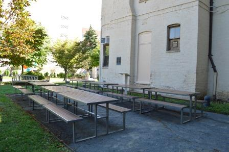 Outdoor classroom space with tables and benches on gravel, with white building to the right and trees to the left