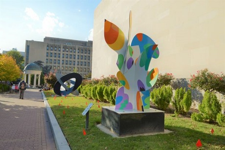 Grassy area with large colorful abstract sculpture and small red flags sticking out of the ground