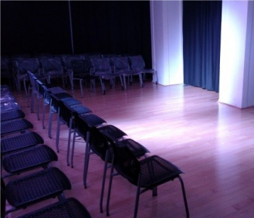 Dimly lit studio space with rows of black chairs facing the stage area