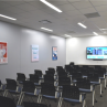 District House Meeting Room with several rows of chairs facing TV screen at front of room