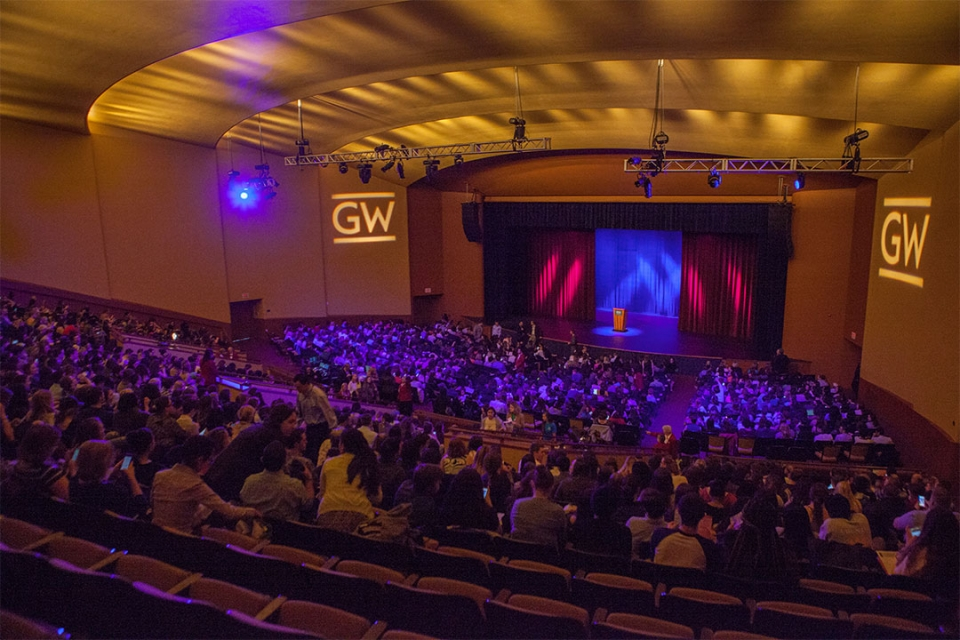 Lisner Auditorium with audience and GW logo on the wall