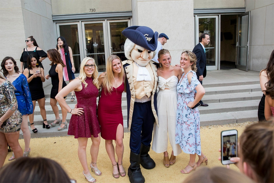 Students taking a picture with George the Mascot infront of Lisner Auditorium