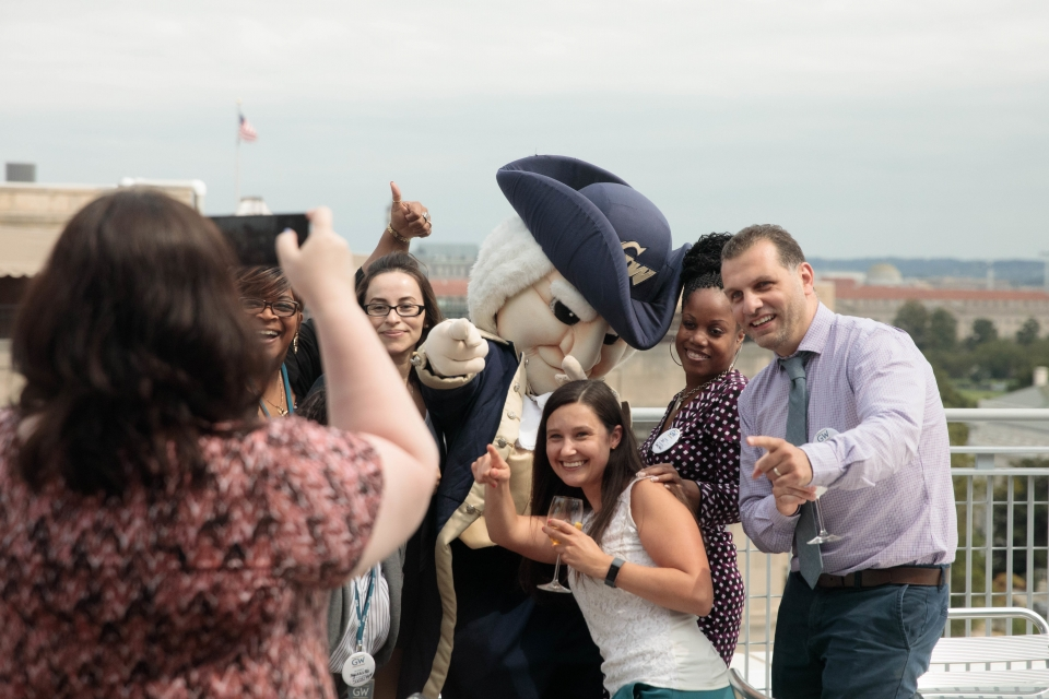 Students posing with George the Mascot on the City View Room Terrace